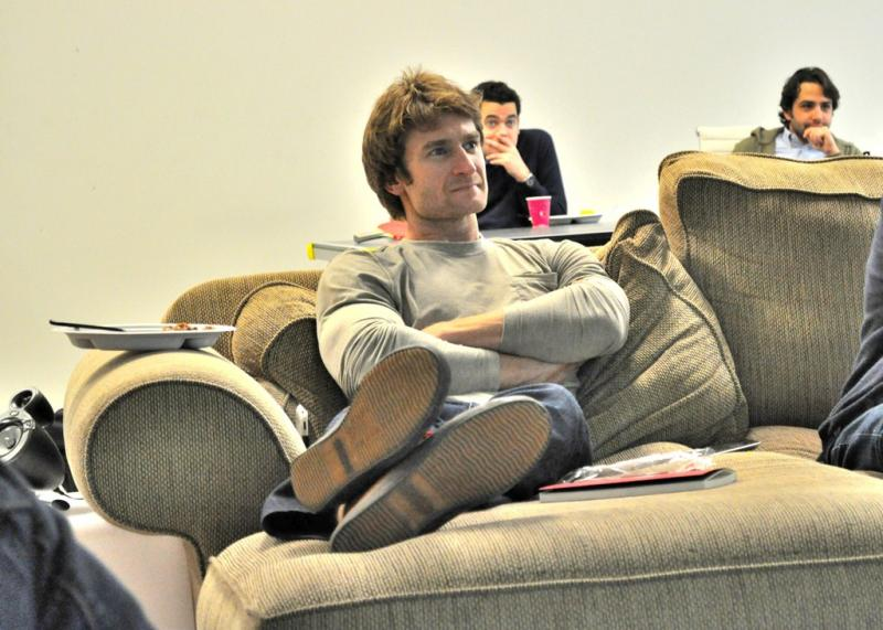 Eric Hinman, a co-founder of Rounded Development, listens to presentations during the company's regular Friday Sparkbook session.