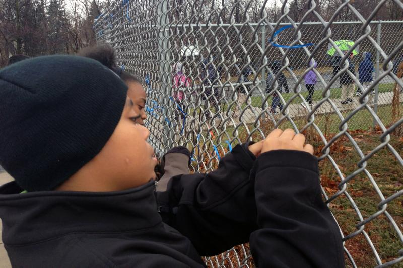 Charles Gibbens, a 5th grader at Southside Academy in Syracuse, ties a ribbon on a fence as part of an anti-bullying program.
