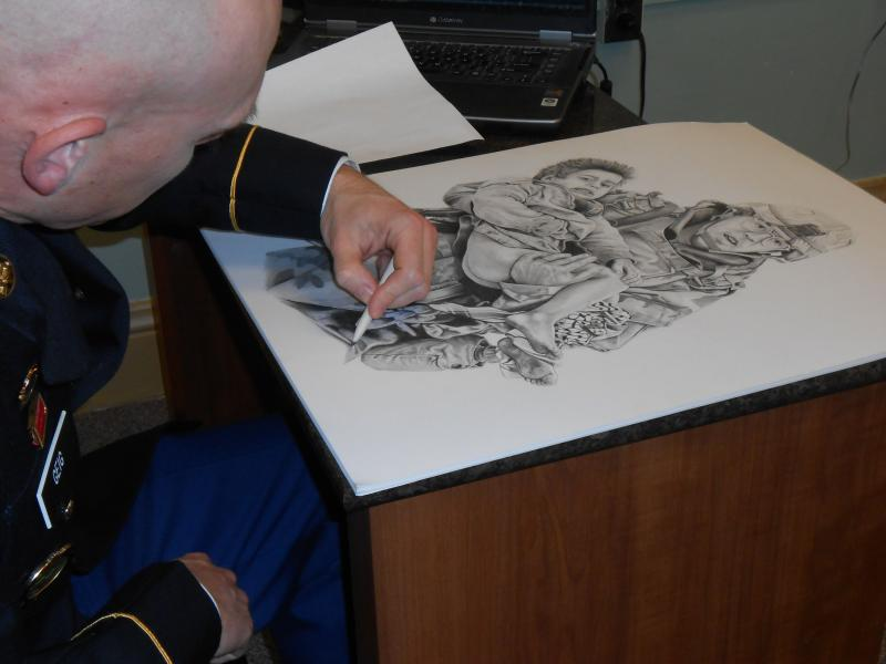 Sergeant 1st Class David Geig creates a drawing of Private 1st Class Joseph Dwyer for display in the Vets Outreach Center.