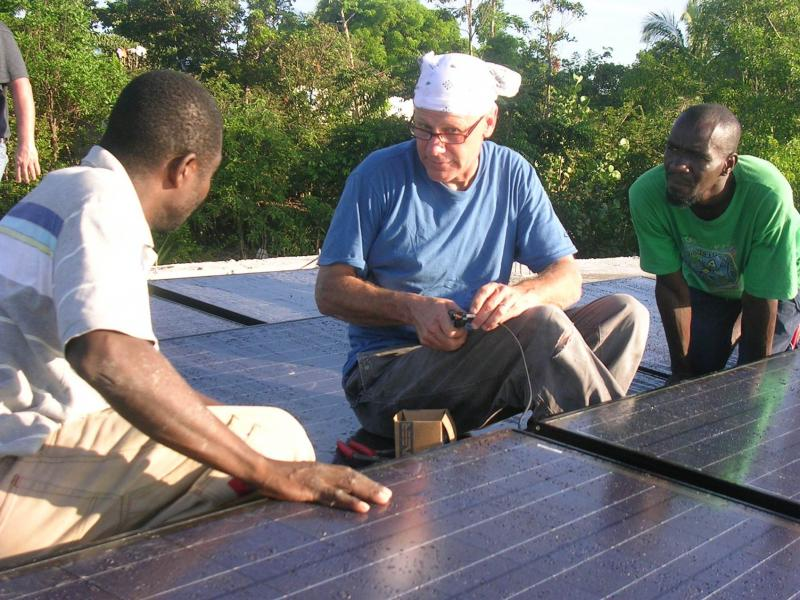 Chris Flatau, Solar Liberty Foundation electrician, trains Haitian technicians on how to install solar electric panels.