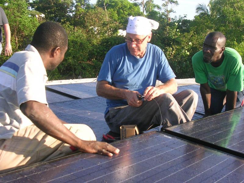 Chris Flatau, Solar Liberty Foundation electrician, trains Haitian technicians on how to install solar electric panels.