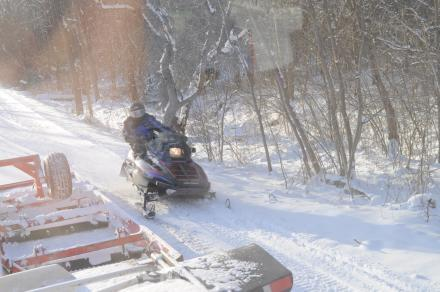 A snowmobile passes a trail groomer along a stretch by the Erie Canal in Oneida County.