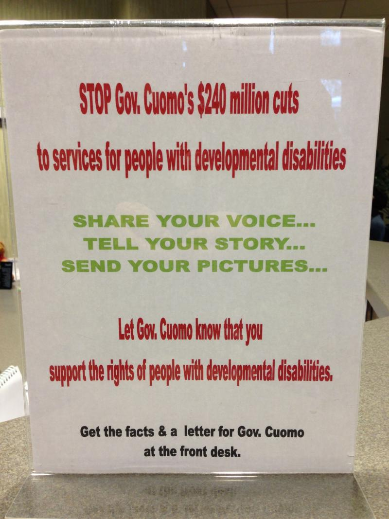 A sign at the front desk in the Enable offices asks people to help fight cuts to state aid for the disabled.
