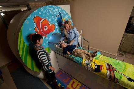 Brain and cognitive sciences research assistants talk to 4-year-old Mason Ray