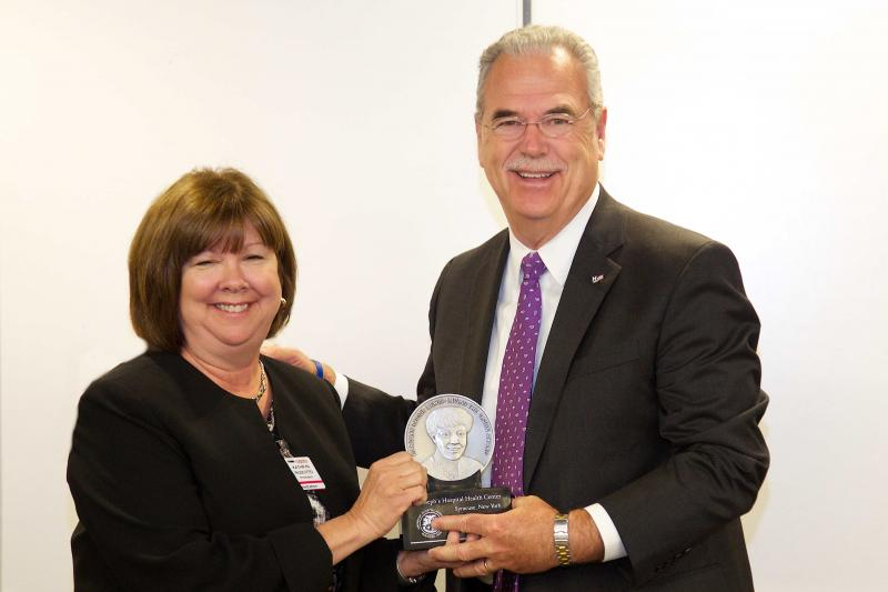 Kathryn Ruscitto, president of St. Joseph's Hospital, is presented an award by Richard Umbdenstock, president of the American Hospital Association