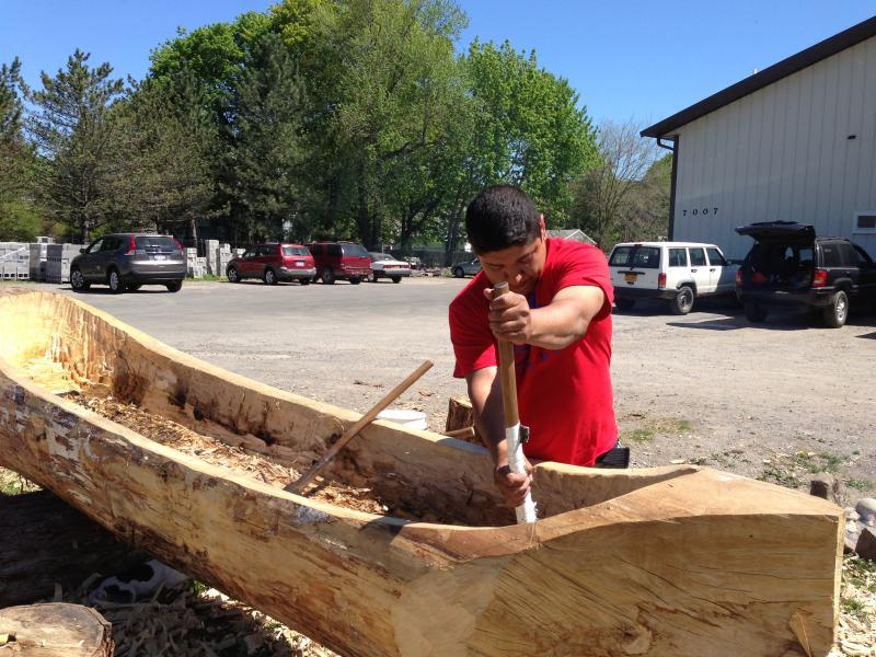 Hickory Edwards of the Onondaga Turtle Clan carves out a Tulip Poplar with an adze as part of a centruies old method of canoe making.