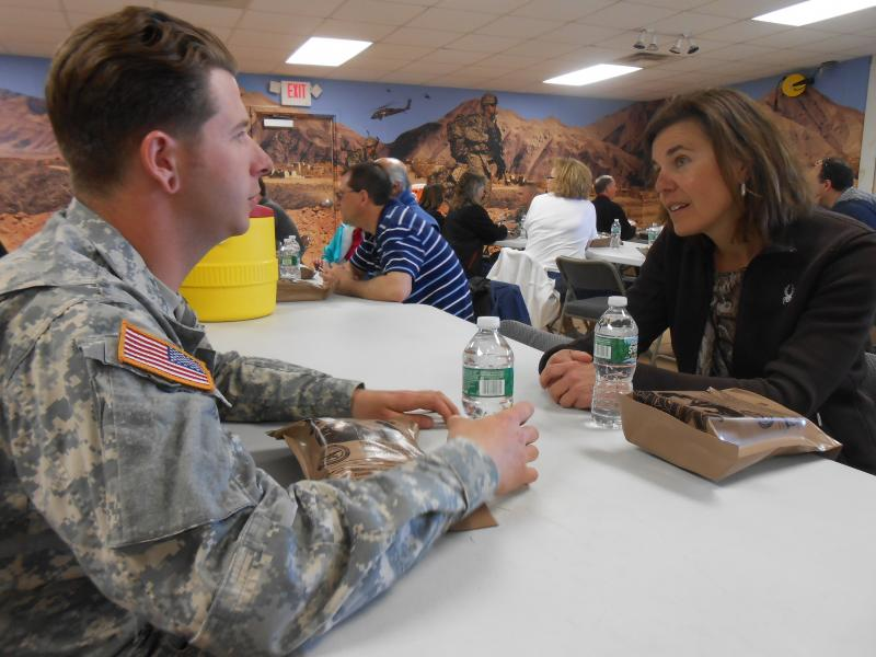 Watertown City Manager Sharon Addison speaks with a soldier over a lunch of MREs - meals ready-to-eat.