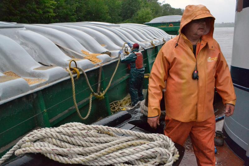 Tugboat Margot engineer Lee Palmateer and deck hand Kenson Delacruz (background) dock a barge along the Oswego Canal.