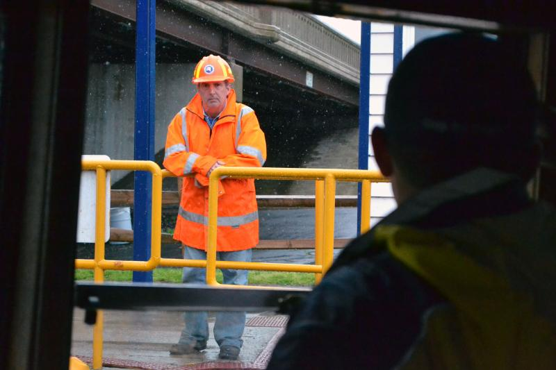 The tugboat Margot's first mate, Sam Zapadinsky, talks to a canal worker at a lock on the Oswego Canal.