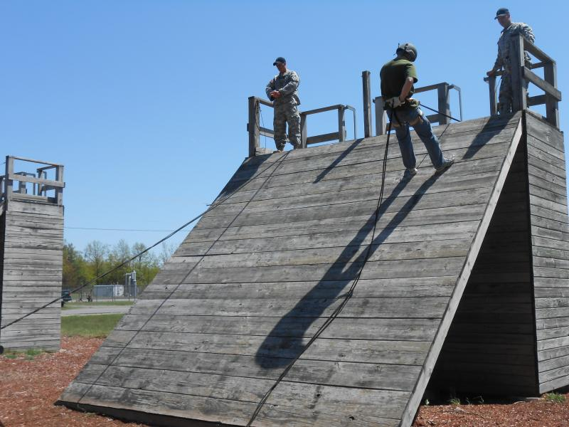 A civilian rappels down a slant wall. This is a part of training in the air assault course, which prepares soldiers to work with helicopters.