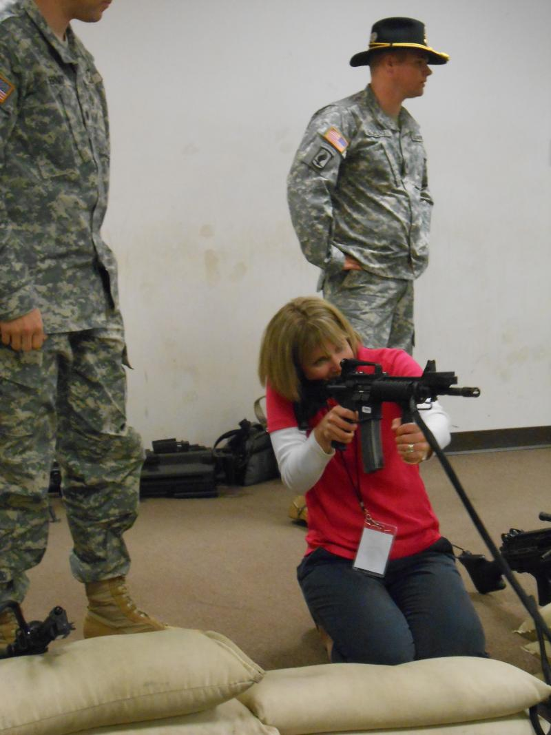 A civilian tries out a modified M-4 in a weapons simulation facility.