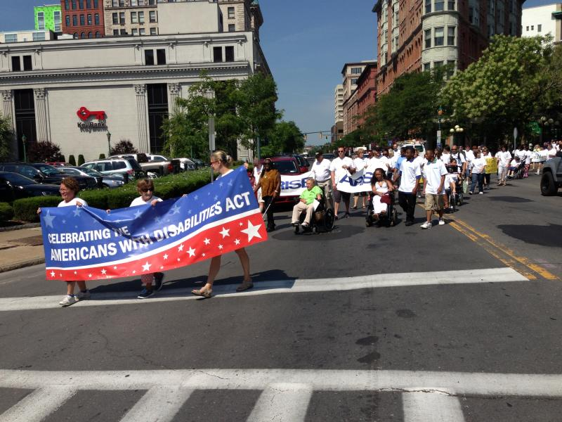 ADA advocates march down East Washington St. in Syracuse during a celebration of the 23rd anniversary of the signing of the Americans with Disabilities Act.