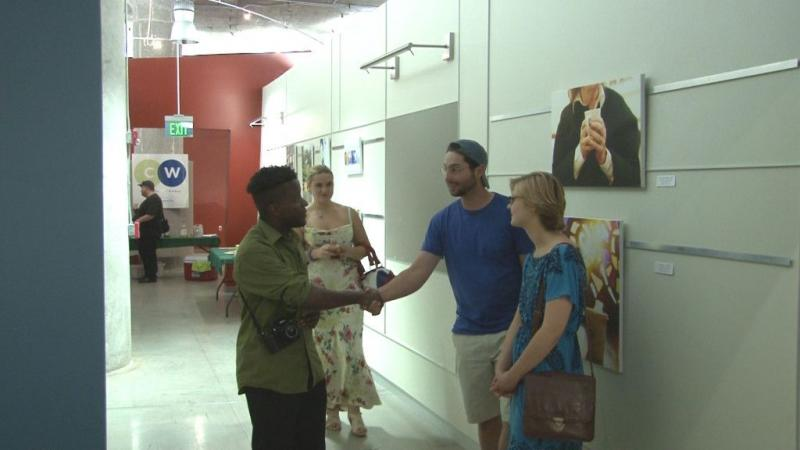 Photographer Jason DeBose greets visitors to his exhibit at The Tech Garden