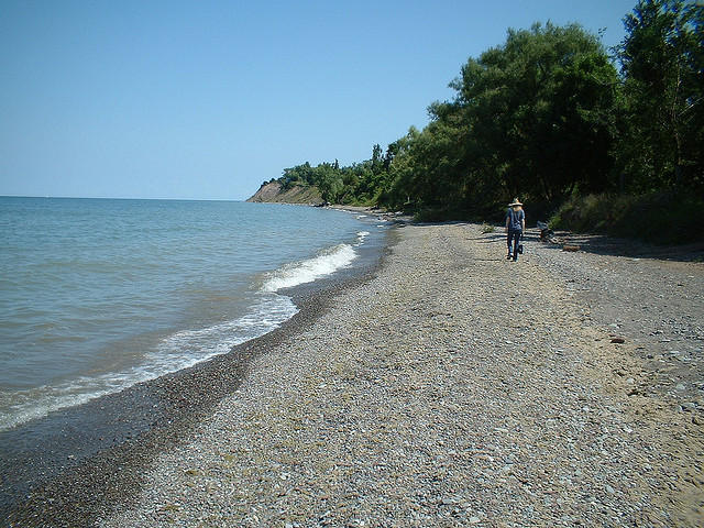 A visitor walks along the Lake Ontario shoreline.