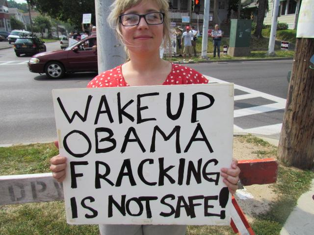 A protester holds a sign about hydrofracking.