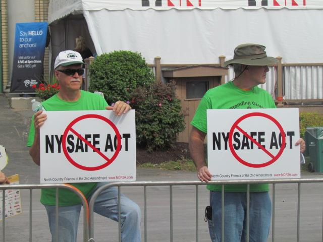 Protesters stand with signs calling for the repeal of the NY Safe Act.