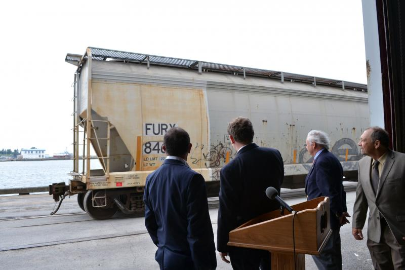 Reps. Richard Hanna (R-Barneveld), left, and Dan Maffei (D-Syracuse), center, pause during a press conference to watch rail cars pass at the Port of Oswego.
