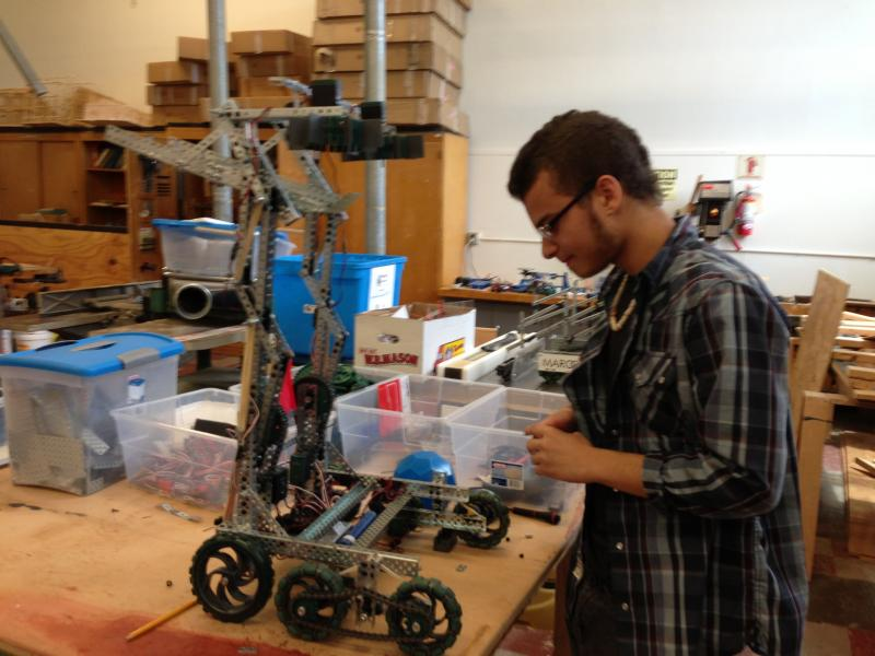 Malik Warden, a junior, working on his robot
