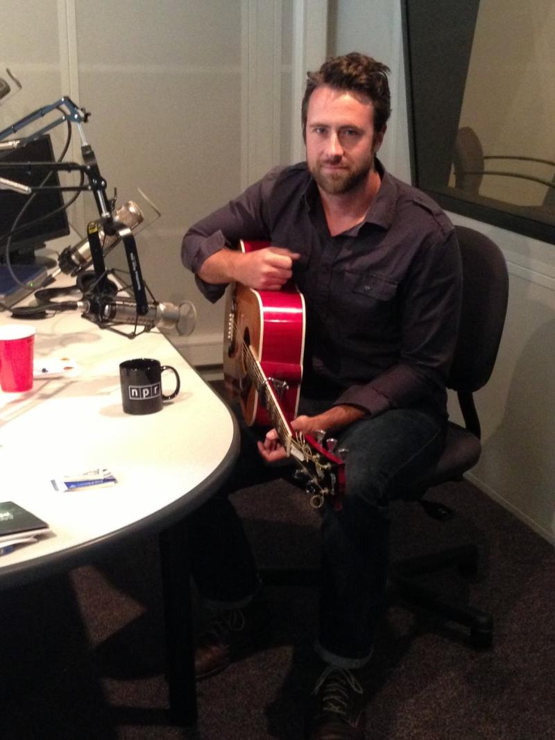 Jay Nash with his guitar in studio with WRVO's Catherine Loper.