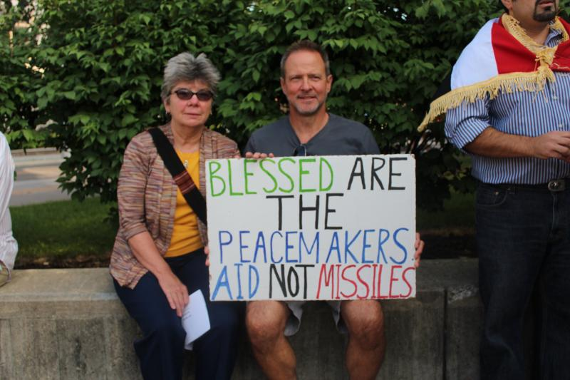 Two protesters hold a sign during a peace vigil at Syracuse University.