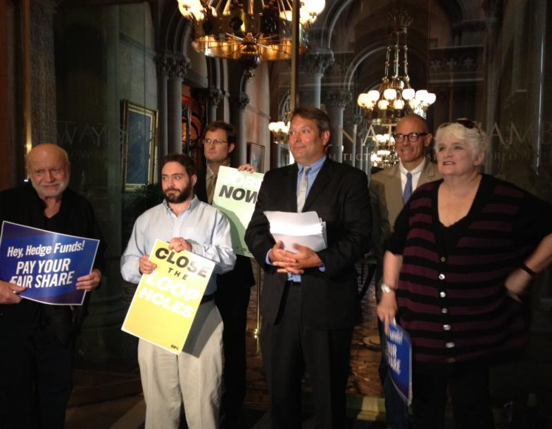 Members from several progressive groups hold signs during a press conference.