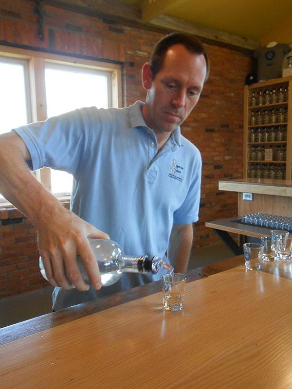 Michael Aubertine pours out a sample of one of his spirits at the Clayton Distillery.
