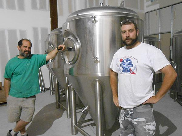 Mark Crandall (left) and Ryan Chaif, of Skewed Brewing, take a break from working on the business's home-to-be in Watertown's mall the summer before it opened. Craft-beer lover Chaif says he'll drink a Pabst Blue Ribbon or two when he does yardwork.