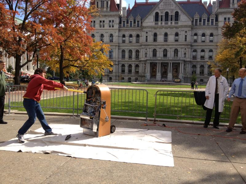 Anti-gambling activists smash a slot machine during a protest in front of the State Capitol.