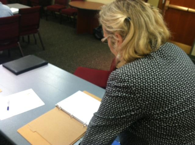 An attendee looks over an information booklet during an Energy Challenge meeting in Oswego.