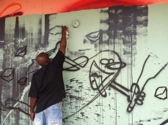 A graffiti artist paints on an outer wall of the building.