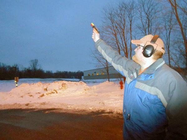 Cody Baciuska, of Loomacres Wildlife Management, fires pyrotechnics into the sky to scare away Watertown's winter crow flock in 2012.