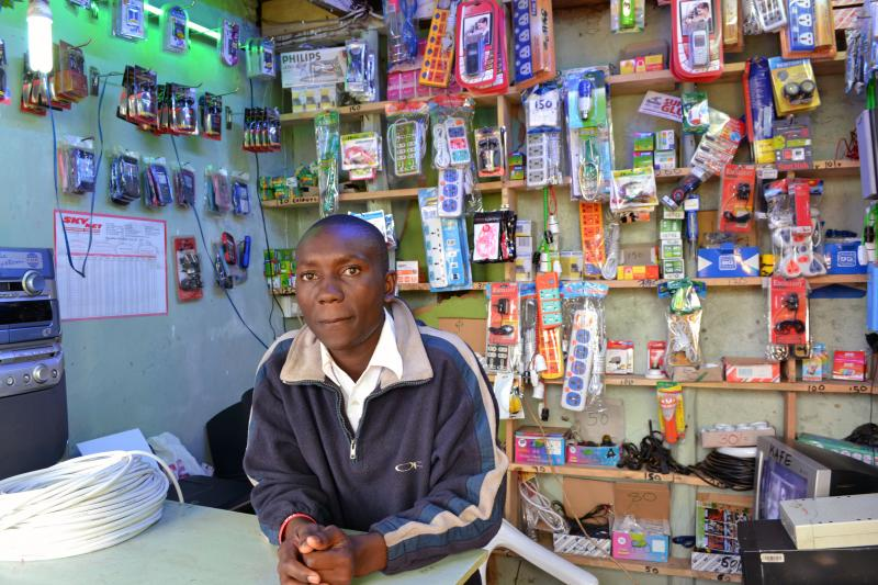 Swalleh Abdullahi tending a small shop that sells mobile phones and an array of cords and cables in the Kibera section of Nairobi.