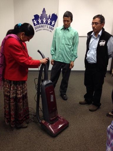 At Journey's End Refugee Services, Bishnu Adhikari, right, tests his students on their vacuum skills.