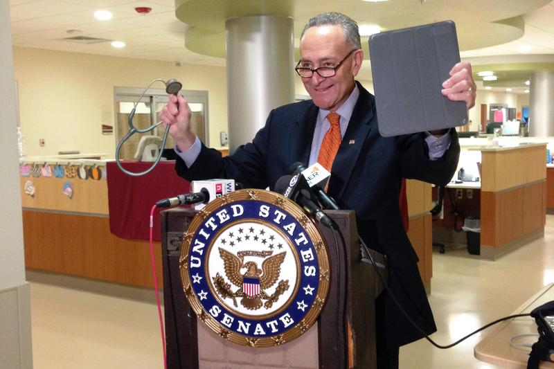 Sen. Charles Schumer stands with a stethoscope and iPad to illustrate how technology will be part of this program.