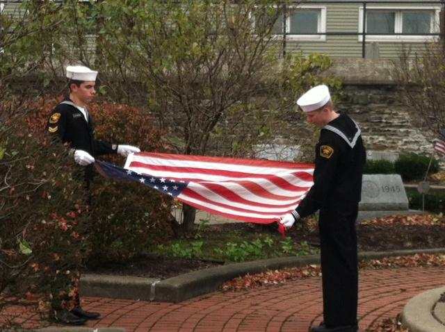 Two cadets fold the American flag before giving it to Oswego Mayor Thomas Gillen.