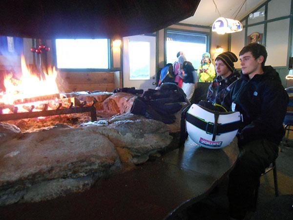 Josh Askins and a friend cozy up to the fire in the clubhouse at Dry Hill Ski Area, Watertown.