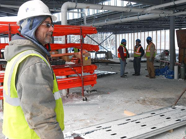 Bart Young, foreman on the construction site, points out the residence hall's features.