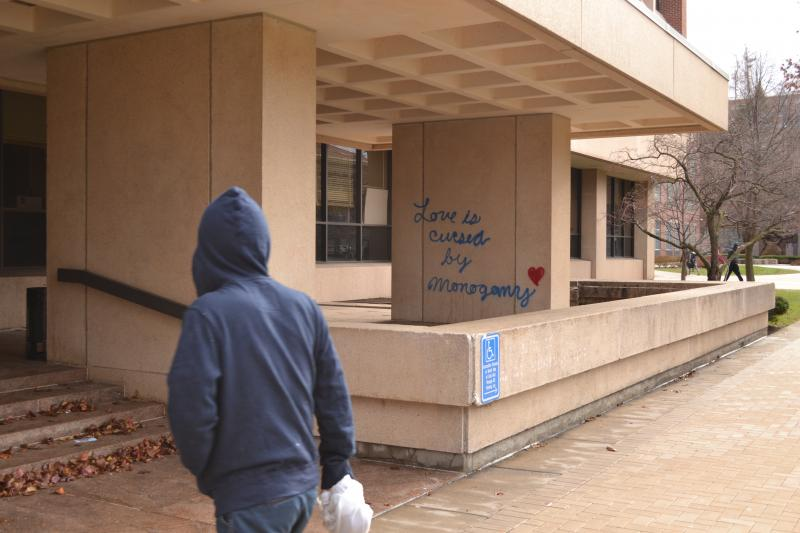 A student walks into Link Hall, one of the buildings vandalized with spray paint.
