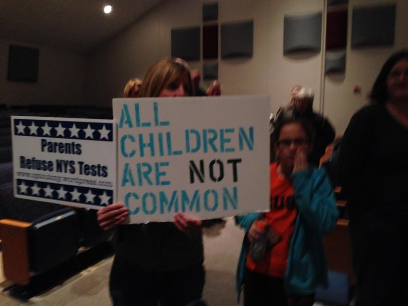 Those attending the Common Core meeting brought signs showing disapproval with the nationwide curriculum.