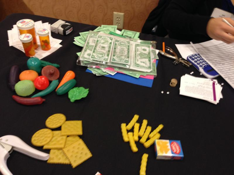 Items are displayed on a table during the poverty simulation.