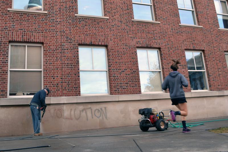 A Syracuse University student jogs past Eggers Hall as a maintenance worker tries to remove graffiti left on the building.