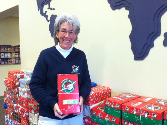 Patty Jennings poses with one of many boxes collected at Oswego Alliance Church for Operation Christmas Child.