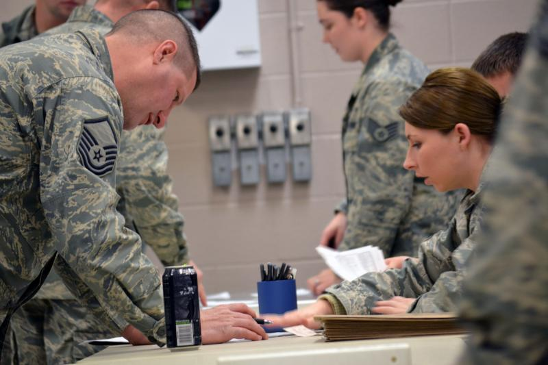 Members of the 174th Air National Guard Attack Wing file paperwork before assisting with the blizzard in western New York.
