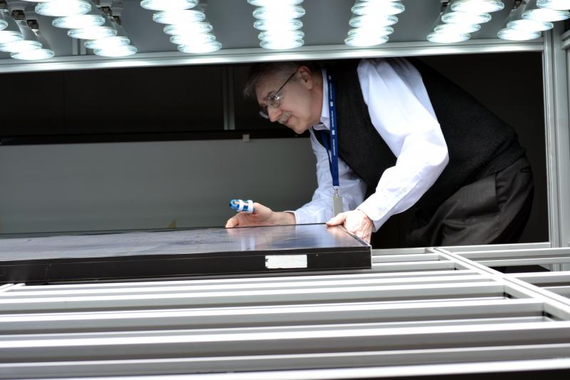 Rick Lewandowski, executive director of CECET, loads a solar panel in a testing lab in Cortland, N.Y.