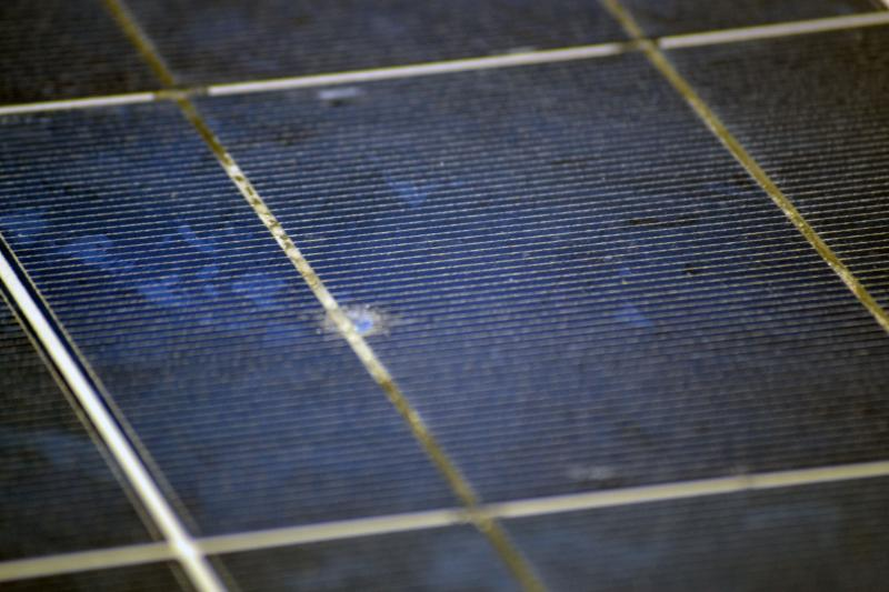 Damage in a solar panel from a two inch piece of ice traveling at 80 mph.