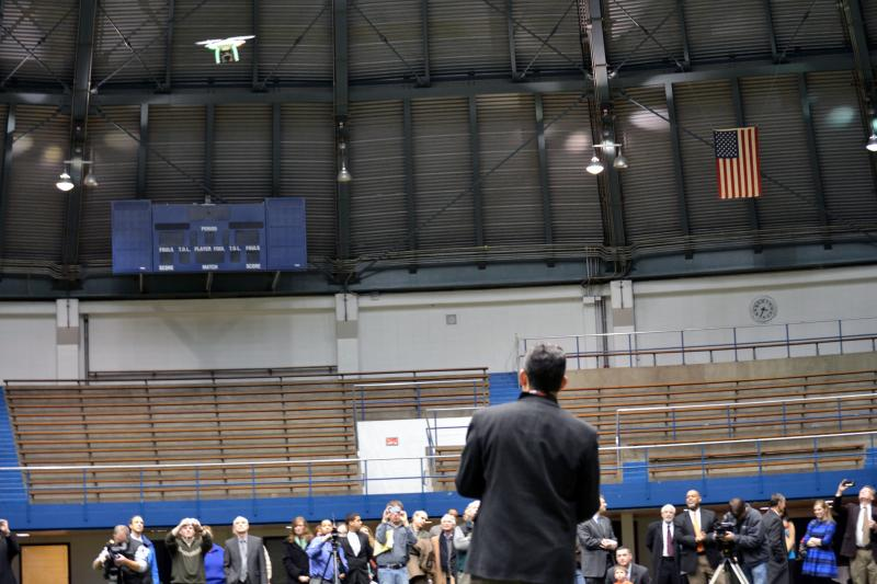Dan Pacheco (foreground), a professor at Syracuse University, demonstrates a small drone at Manley Field House.