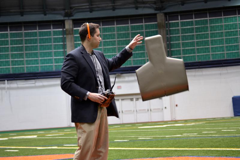 Joe Kumer, of Propulsive Wing, demostates his drone from elected officials Friday at Syracuse University.