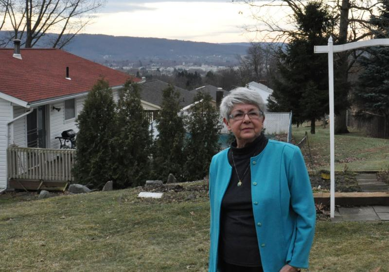 Wanda Hudak at home in Endicott with the former IBM campus in the background.