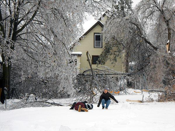 Kids play amid downed tree limbs in Watertown after last month's ice storm.