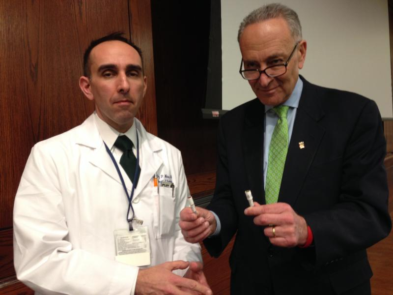 Sen. Charles Schumer and Dr. Anthony Weiss holding vials of Biologic during a news conference at Weiskotten Hall in Syracuse Monday.